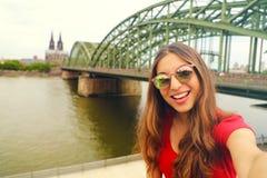 Foto de Selfie da mulher nova da forma na água de Colônia com ponte de Hohenzollern e catedral no fundo, água de Colônia, Alemanh fotos de stock