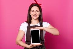 Foto de soportes femeninos atractivos jovenes con sonrisa dentuda y artilugio de las demostraciones el nuevo sobre fondo rosado V fotos de archivo libres de regalías