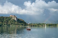 Foto de surpresa do lago sangrada na noite ap?s a chuva com o arco-?ris vibrante no c?u e nos pares no barco de madeira imagens de stock