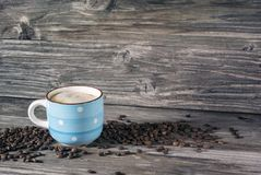 Foto de um copo azul do café perfumado em um fundo de feijões de café e de uma tabela de madeira fotografia de stock