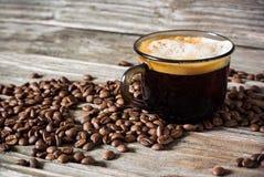 Foto de um copo do café preto perfumado em um fundo de feijões de café e de uma tabela de madeira fotografia de stock royalty free