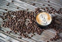 Foto de um copo do café preto perfumado em um fundo de feijões de café e de uma tabela de madeira Vista superior fotografia de stock