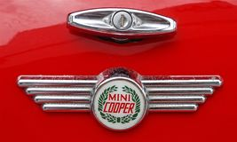 Foto de um crachá retro do logotipo do carro de Mini Cooper em um carro vermelho de Mini Cooper imagem de stock