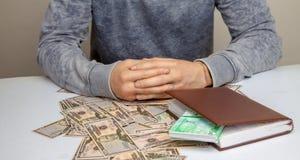 A foto de um homem senta-se em uma tabela empilhada com dinheiro Fotos de Stock Royalty Free