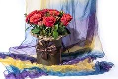 Foto de um ramalhete das flores em um vaso marrom em um lenço da cor isolado no branco fotos de stock royalty free