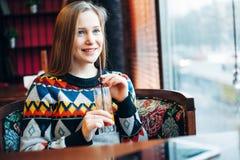 Foto de um suco bebendo da mulher através da janela Fotografia de Stock Royalty Free
