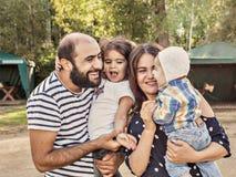 Foto de uma família feliz O paizinho da mamã recém-nascido e a menina da criança de quatro anos passam o tempo no parque no verão imagem de stock