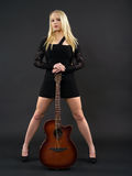 Fêmea que está com guitarra acústica Foto de Stock Royalty Free