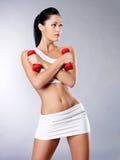 Foto de uma jovem mulher saudável do treinamento com dumbbells Fotografia de Stock Royalty Free