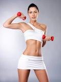 Foto de uma jovem mulher saudável do treinamento com dumbbells Fotografia de Stock