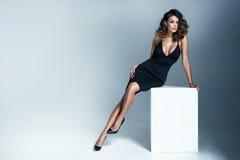 Foto de uma mulher moreno 'sexy' que veste o vestido preto Fotografia de Stock Royalty Free
