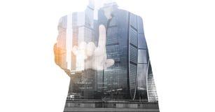 Foto de un dedo índice de un hombre de negocios acertado en un traje y los edificios de oficinas, rascacielos de una ciudad una e imagenes de archivo
