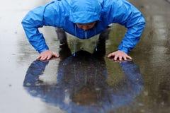 Foto de una mujer atlética joven que ejercita en la lluvia Foto de archivo libre de regalías