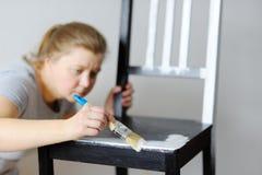 Foto de una mujer atractiva que pinta las sillas en el cuarto Imágenes de archivo libres de regalías