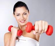 Foto de una mujer joven del entrenamiento sano con pesas de gimnasia Foto de archivo