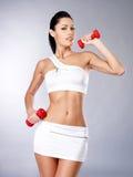 Foto de una mujer joven del entrenamiento sano con pesas de gimnasia Imágenes de archivo libres de regalías