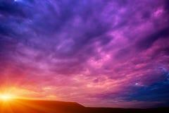 Foto de una puesta del sol violeta con las nubes Fotografía de archivo libre de regalías