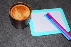 Foto de una taza de café en un fondo de un tablero magnético y de rotuladores Un color saturado del café con una espuma airosa y  foto de archivo