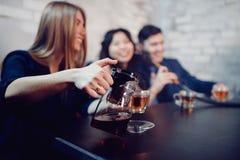 Foto Defocused La muchacha toma la casa de huéspedes, el té de colada y la sonrisa ampliamente Concepto de reuniones caseras, reu imágenes de archivo libres de regalías