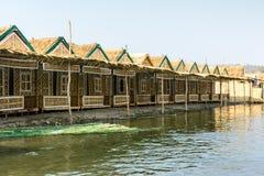 Foto degli alloggi di bambù accanto al fiume dell'uomo, alla pagoda stabilita di Shwe Taw, il Myanmar Fotografie Stock Libere da Diritti