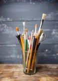 Foto dei pennelli in un vetro che sta sulla vecchia tavola di legno, Fotografie Stock Libere da Diritti