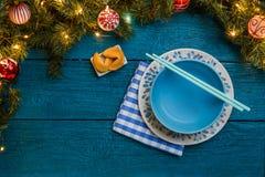 Foto dei rami di abete, biscotti con la previsione, piatti, bastoni del nuovo anno per i sushi Immagine Stock Libera da Diritti