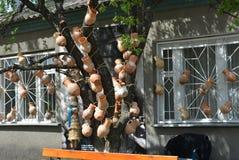 Foto del árbol viejo adornado con la arcilla ucraniana de diversos colores y de dibujos delante de la casa Imagen de archivo libre de regalías