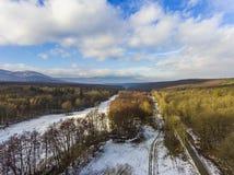 Foto del abejón del bosque y de prados nevosos en invierno con las nubes en el cielo azul y las colinas en el fondo Imagen del ab Fotos de archivo libres de regalías
