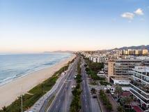 Foto del abejón de la salida del sol en la playa y el paseo marítimo, edificios frente al mar de Barra da Tijuca que cogen la luz Foto de archivo