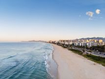 Foto del abejón de la salida del sol en la playa y el paseo marítimo, edificios frente al mar de Barra da Tijuca que cogen la luz Fotografía de archivo libre de regalías