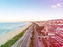 Foto del abejón de la salida del sol en la playa y el paseo marítimo, edificios frente al mar de Barra da Tijuca que cogen la luz Fotografía de archivo