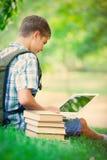 Foto del adolescente hermoso con el ordenador portátil y los libros en el wonderfu Imagen de archivo