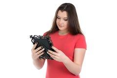Foto del adolescente que mira el marco de la foto Fotos de archivo