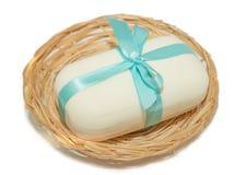 Foto del aislamiento del jabón con un arco en una cesta en un backgr blanco Fotos de archivo libres de regalías