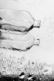 Foto del arte de la botella de cristal en el espejo con agua Fotos de archivo