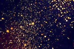 Foto del brillo de oro en un fondo negro Explosión de oro Imágenes de archivo libres de regalías