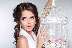 Foto del concepto de la mujer sorprendente que sostiene la jaula de pájaros del vintage aislada Imagen de archivo
