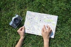 Foto del concepto del viaje con el mapa de la ciudad europea vieja y el finger y la cámara vieja de la mujer imagen de archivo