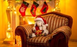 Foto del cordero del juguete que se sienta en silla en la chimenea en Christma Imágenes de archivo libres de regalías