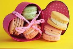 Foto del dessert Macarons sul backround giallo Foto dell'alimento Dessert nella scatola Scatola nella forma del cuore Fotografia Stock Libera da Diritti