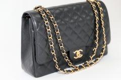 Foto del editorial negro de la marca del bolso de Chanel en el fondo blanco foto de archivo