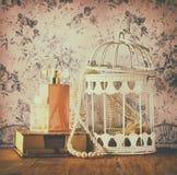 Foto del estilo del vintage del collar y del perfume viejos de la perla sobre fondo del estampado de flores imagen filtrada retra fotografía de archivo