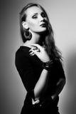 Foto del estudio de la mujer joven en el fondo blanco Negro y pizca Imagenes de archivo