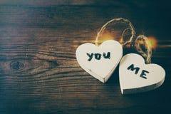 Foto del foco selectivo de los pares de corazones de madera con palabras usted, yo escrito en ellas Foto de archivo libre de regalías