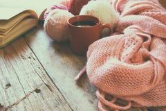 Foto del fuoco selettivo della sciarpa tricottata accogliente rosa con alla tazza di caffè, le palle del filato di lana ed il lib Immagini Stock Libere da Diritti
