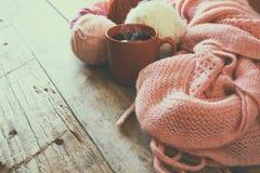 Foto del fuoco selettivo della sciarpa tricottata accogliente rosa con alle palle del filato di lana e della tazza di caffè su un Fotografia Stock