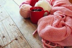 Foto del fuoco selettivo della sciarpa tricottata accogliente rosa con alle palle del filato di lana e della tazza di caffè su un Immagini Stock