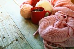 Foto del fuoco selettivo della sciarpa tricottata accogliente rosa con alle palle del filato di lana e della tazza di caffè su un Fotografia Stock Libera da Diritti
