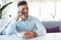 Foto del hombre adulto hermoso que habla en el teléfono móvil negro, cuando Foto de archivo libre de regalías