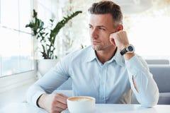 Foto del hombre confiado adulto 30s que se sienta solamente en café de la ciudad con Fotografía de archivo